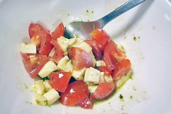 ブリーチーズとトマトをダイス状にコロコロと小さくカットしてバジルのジェノベーゼソースで和えます