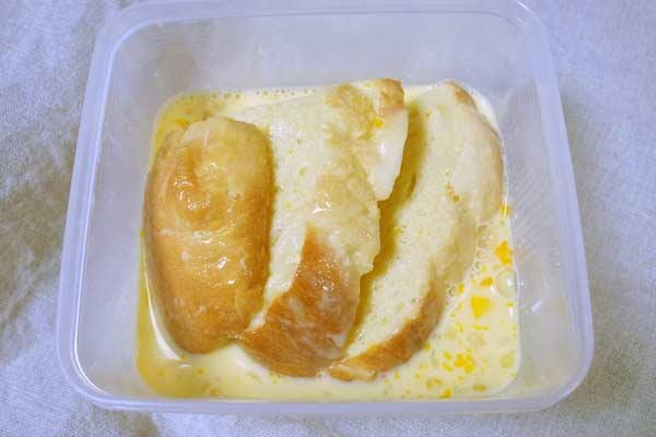 タッパー容器に入った卵液に浸かったフランスパン3切れ