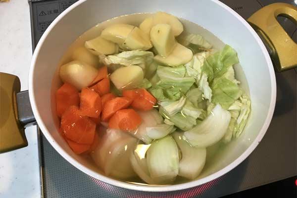 水、洋風だしのもとを入れた鍋に野菜を入れて火にかける