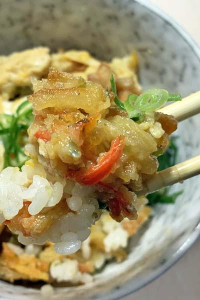 業務スーパーかき揚げ丼を箸で持ち上げる
