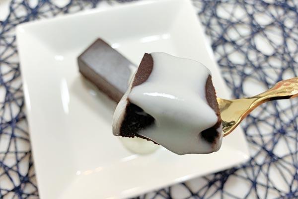 リッチショコラケーキのヨーグルトがけをフォークて持ち上げたところ