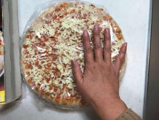 箱から出したピザの大きさを女性の手と比較