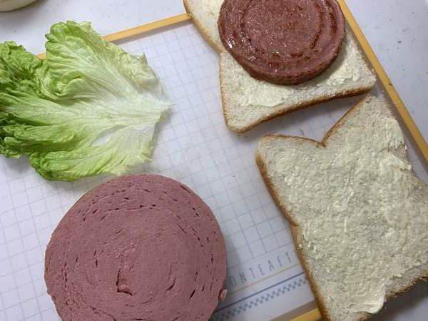 食パンにランチョンミートやレタスを挟んでいる様子