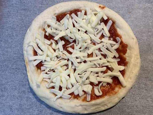 ピザソースを塗ってチーズをのせた業務スーパーのピザ生地