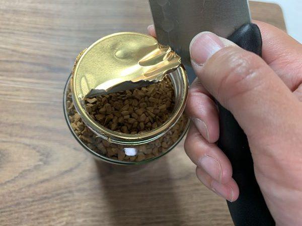包丁の角で業務スーパーインスタントコーヒーの内蓋を開けているところ