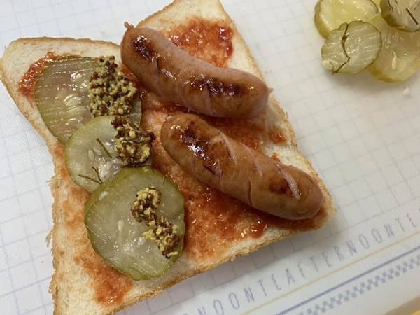 ケチャップとマスタードを塗った食バンにウインナーと業務スーパーのピクルスをのせたところ