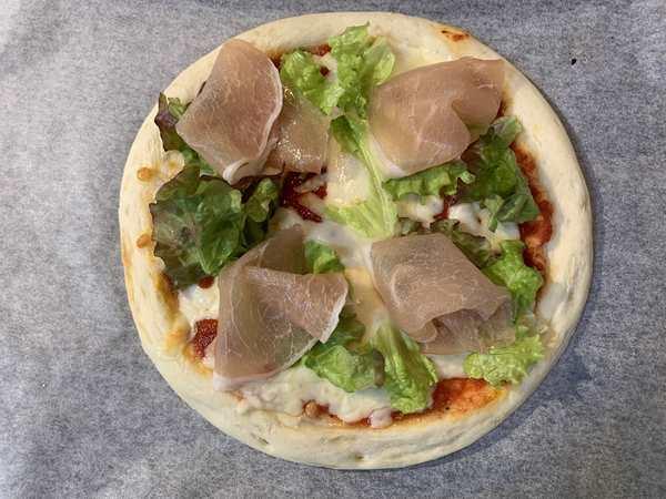 生ハムとサニーレタスをのせた業務スーパーのピザ生地