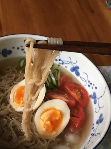 完成した冷麺を箸で持ち上げる様子