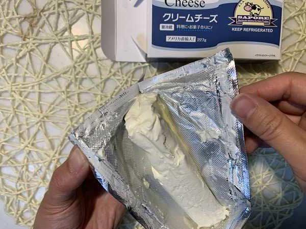 業務スーパークリームチーズの包み紙の横を破く様子
