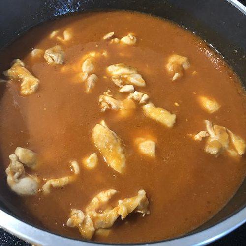 フライパンに入れた鶏もも肉と業務スーパーのバターチキンカレー