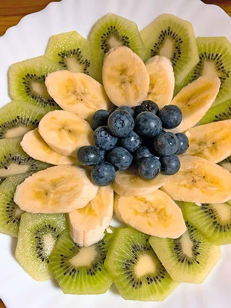 お皿に盛ったキウイ・バナナ・ブルーベリー