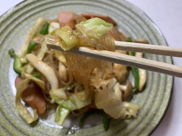 野菜炒めに入っている春雨を箸で持ち上げる様子