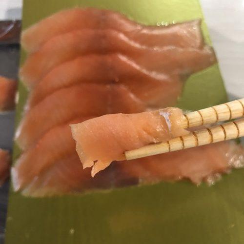箸でつまんだ業務スーパーのスモークサーモン
