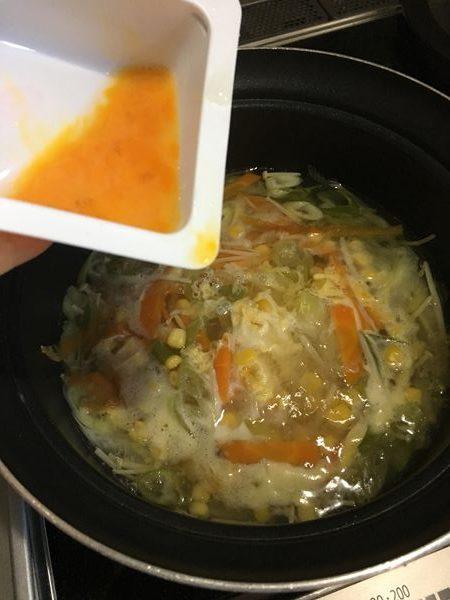 中華スープの材料を煮込んだところに卵を加える様子