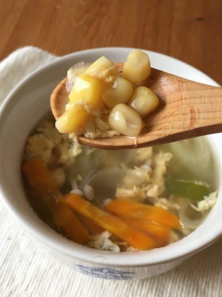 完成した中華スープの中からスプーンですくった業務スーパーのスイートコーン
