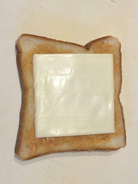 ピーナッツバターを塗った上にチーズをのせた食パン