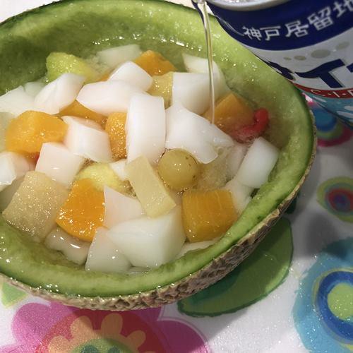 フルーツと杏仁豆腐を入れたメロンの器にサイダーを注ぐ様子