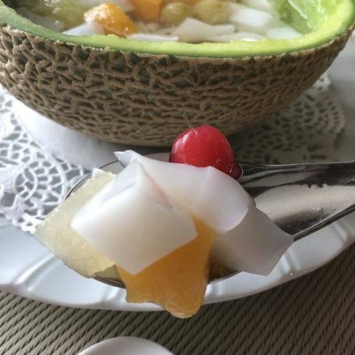 スプーンにのせた杏仁豆腐入りフルーツポンチ