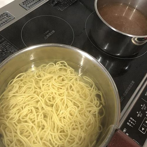 中華麺を茹でてラーメンスープを作る様子