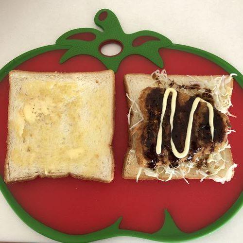 マーガリンを塗った食パンとソース・マヨネーズをかけたアジフライ・キャベツをのせた食パン
