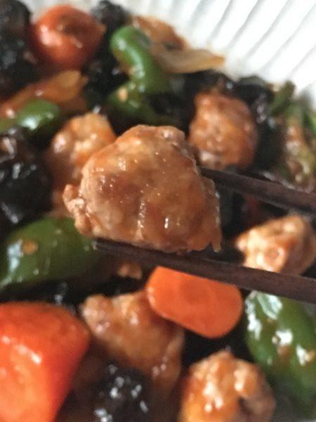 箸でつまんだ酢豚の豚肉