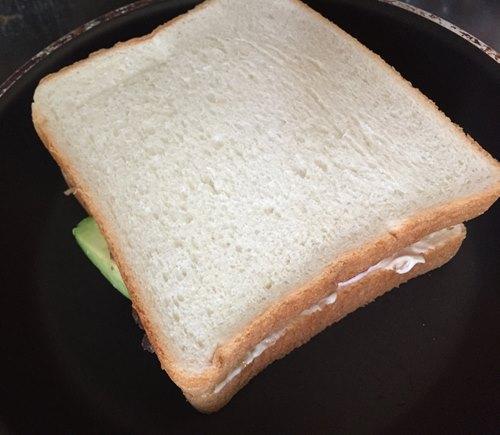 フライパンにのせた具材を挟んだ食パン