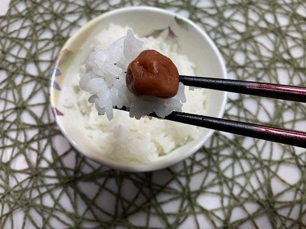 ご飯と業務スーパーの梅干しを箸で持ち上げる様子