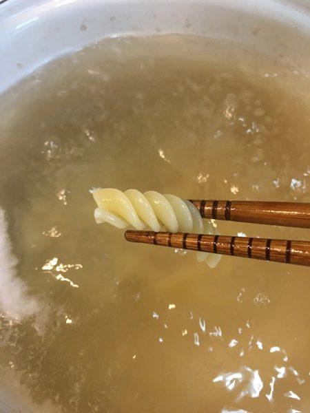 箸でつまんだ茹でた業務スーパーのマカロニ