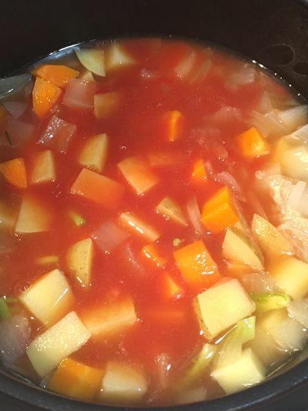 野菜にトマトジュースと調味料を加えて煮る様子