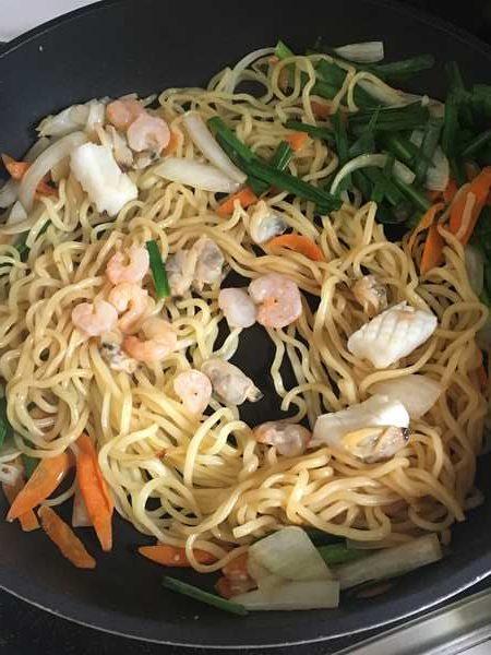 炒めた野菜に加えた焼きそば麺とシーフードミックス