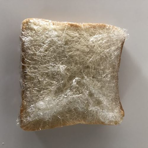 竜田揚げやレタスを挟んでラップに包んだパン