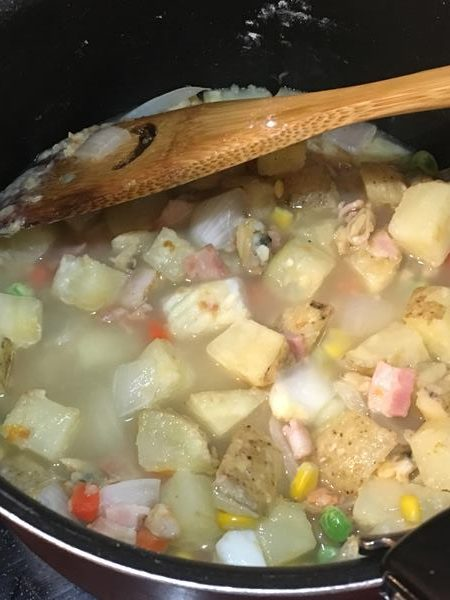 水とコンソメを入れてシチューの具材を煮る様子