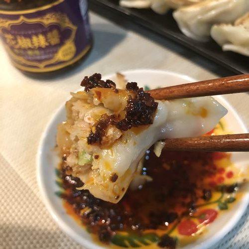 箸で持ち上げた業務スーパーの花椒辣醤つき餃子