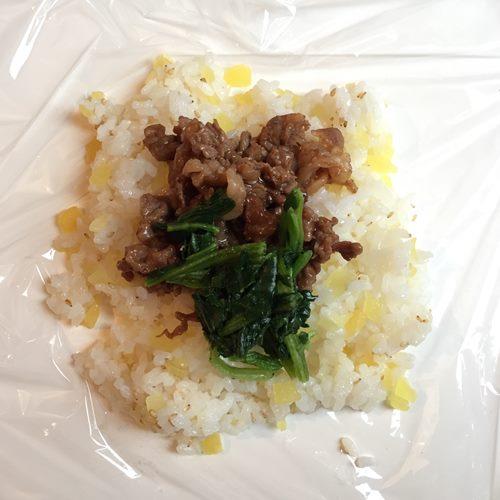 ラップに広げたほうれん草と炒めた牛肉をのせた白ごま・たくあん入りご飯