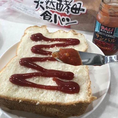 ケチャップを塗った食パンとバターナイフですくったサンバル