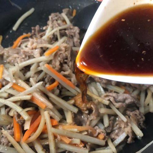 炒めた牛肉と業務スーパーのごぼうにんじんミックスに合わせ調味料を加える様子