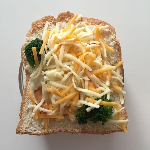 マカロニグラタンを入れたイギリスパンににかけたチーズ
