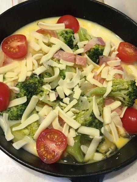 フライパンに入れたキッシュ生地に加えたチーズとミニトマト