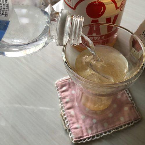 はちみつと業務スーパーのりんご酢を入れたグラスに炭酸水を注ぐ様子