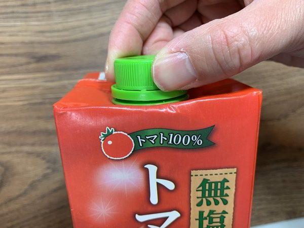 業務スーパーのトマトジュースキャップを指先でつまむ様子