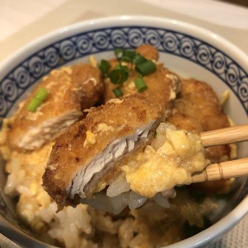 箸ですくったカツ丼のチキンカツ