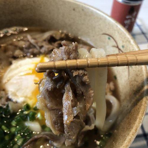 箸で持ち上げた肉うどん