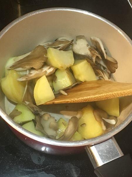 小鍋でじゃがいもと舞茸を炒め合わせる様子