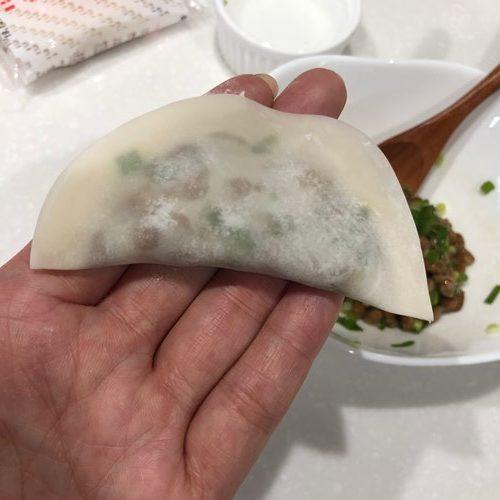 手のひらに乗せた揚げる前の納豆餃子