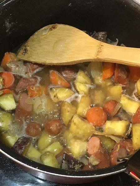 炒めた野菜類・ウインナーに水・出汁の素を入れて煮る様子