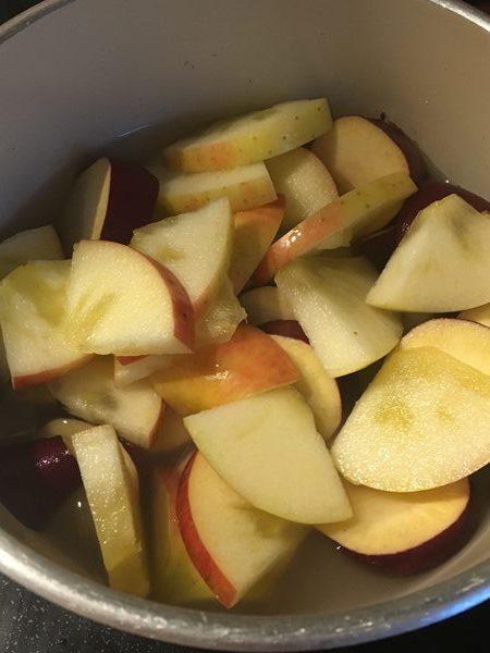 小鍋に入れたサツマイモ・りんご・調味料