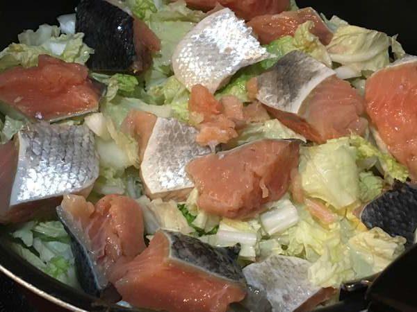 フライパンに敷き詰めた白菜とねぎの上にのせた鮭