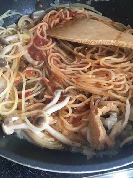 玉ねぎ・しめじ・パスタ・トマトサルサが入ったフライパンに入れた味噌