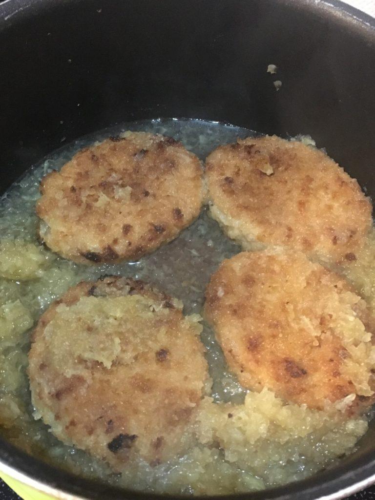 鍋で煮た大根おろしにミートコロッケを入れる