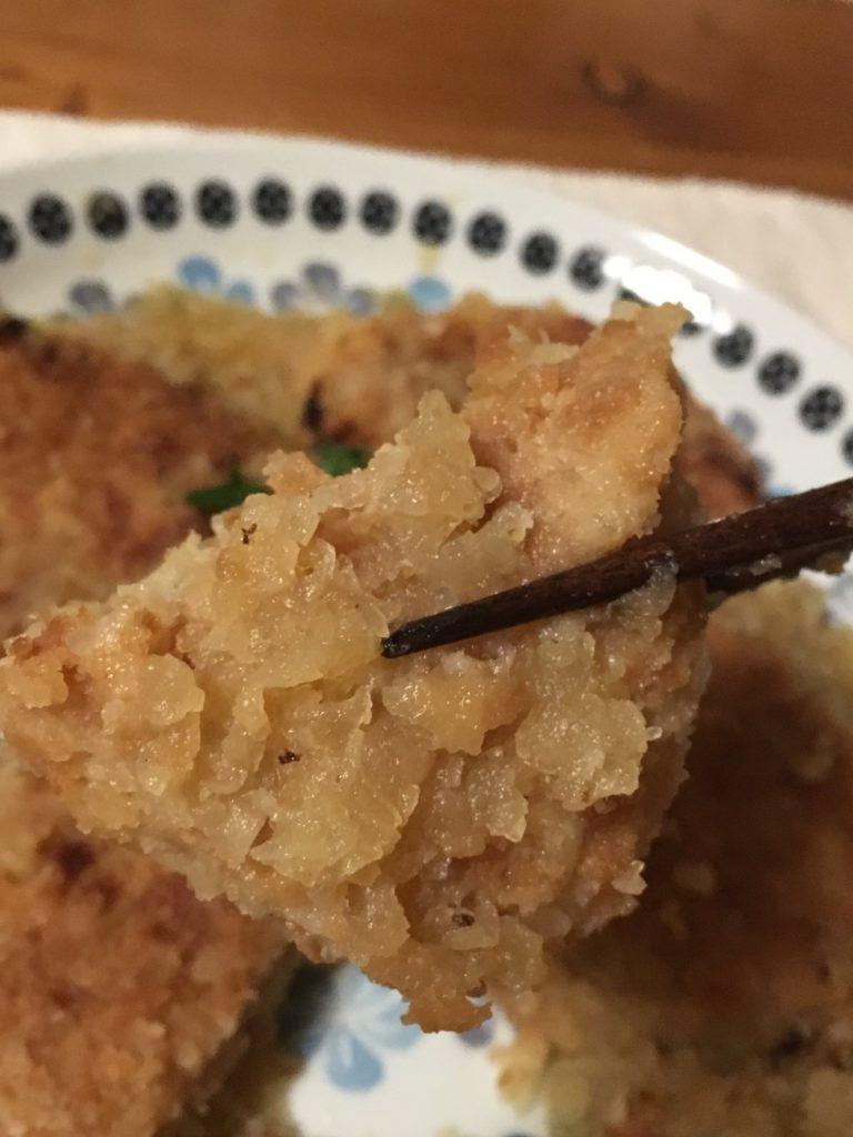 箸で持ち上げたミートコロッケのみぞれ煮